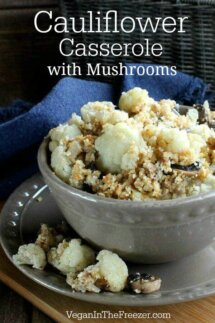 Close up view of a beige bowl overflowing with crumble topped cauliflower and mushrooms.