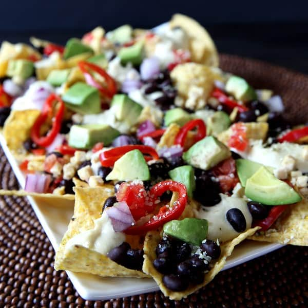 Front angle view of a close up of veggie loaded nachos on a white rectangle plate.