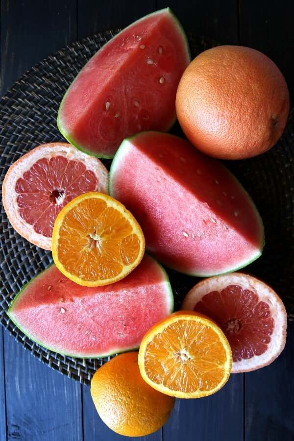 Overhead view of fresh watermelon and citrus cut open on a straw background.
