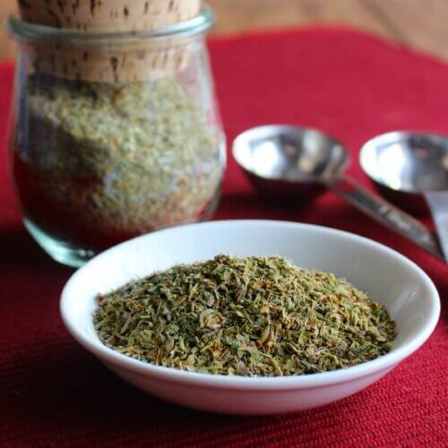 Front view of a tilted mini white plate holdings herbs against a red background.