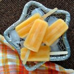 Overhead view of orange popsicles laying on ice in a silver metal basket with a colorful cloth napkin.
