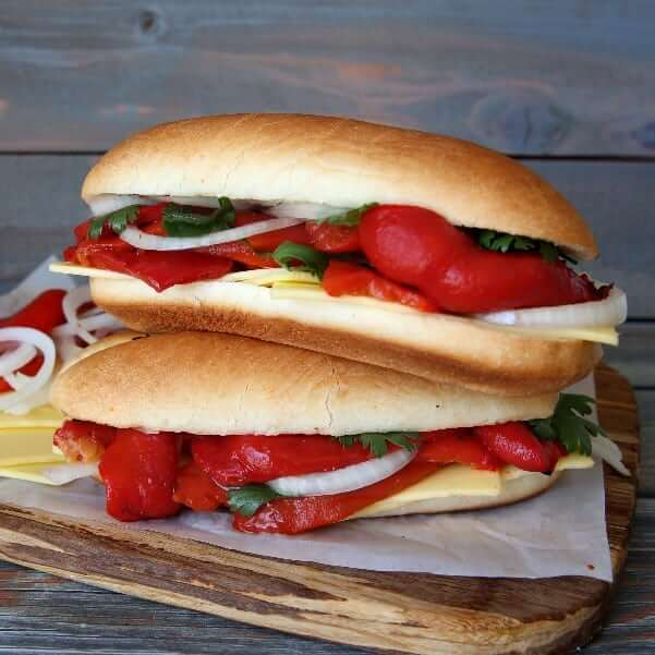Front view photo of double stack stuffed baguette sandwiches on a wooden cutting board.