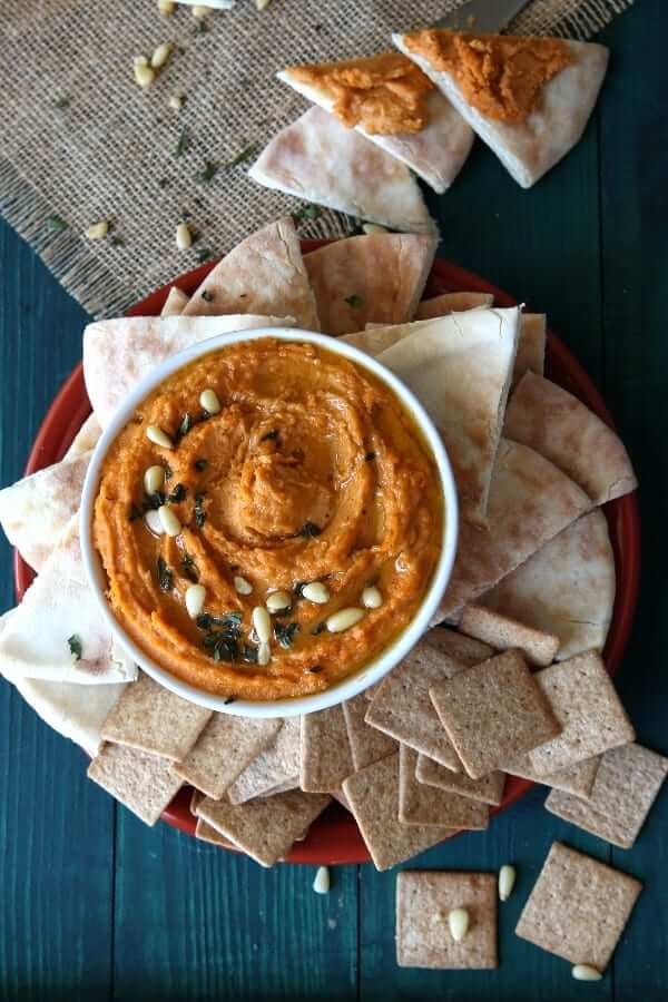 Overhead photo of spicy autumn orange dip on a burnt orange plate surrounded by pita bread triangles and crackers.