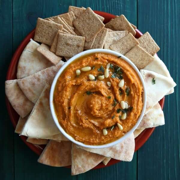 Overhead photo of spicy autumn orange chipotle hummus in a white bowl surrounded by pita bread triangles and crackers.
