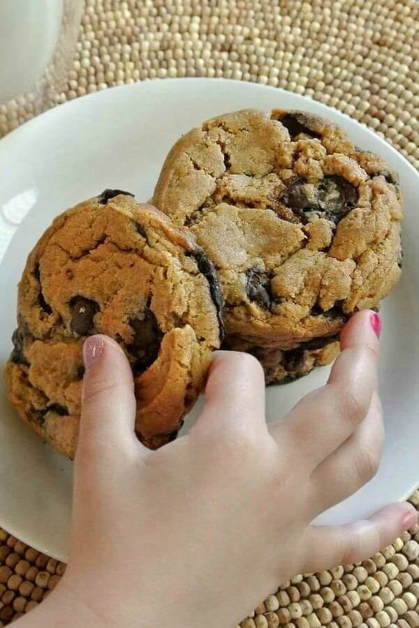 Three giant cookies with one little girls hand picking up the front one.