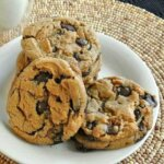 Big fat cookies are piled on a small white plate and beaded mat.