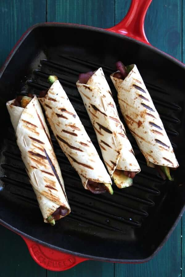 Overhead view of four burritos cooking in a red non stick grill pan.