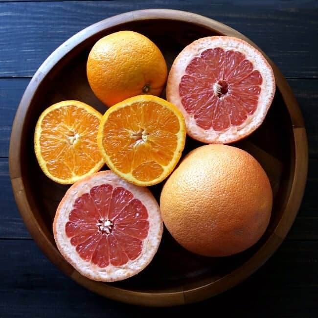 Overhead view of fresh pink grapefruit and oranges with some cut in half.
