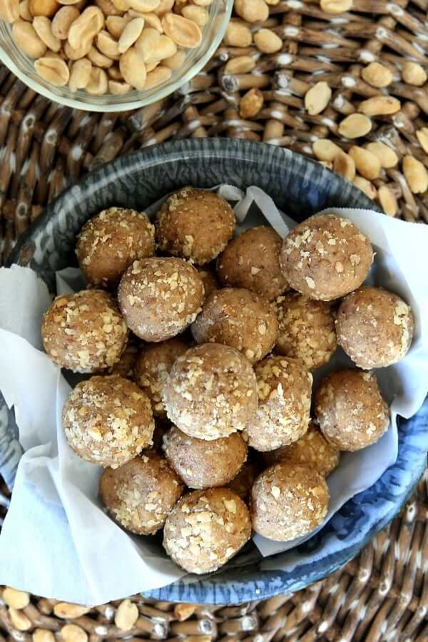 Overhead photo of a gray enamelware bowl lined with parchment and filled with protein peanut butter balls.