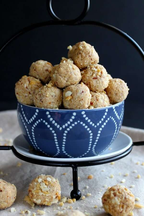 Close up photo os peanut butter energy balls spilling out of a blue and white bowl.