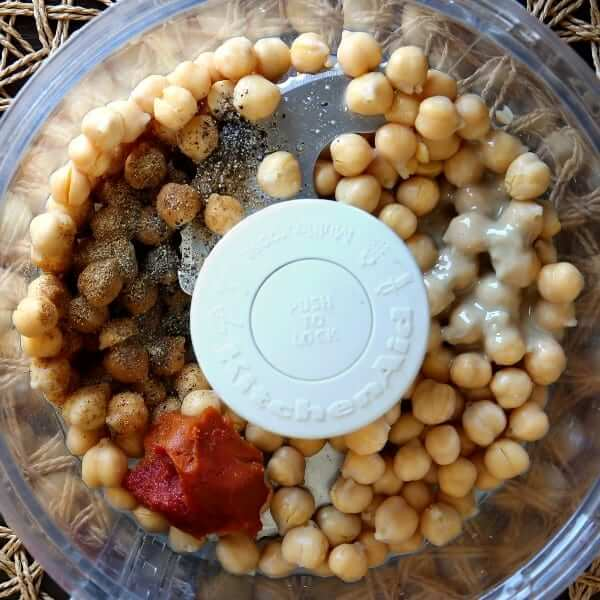 Overhead ohoto of chickpeas and the remaining ingredients for spicy hummus in a food processor.