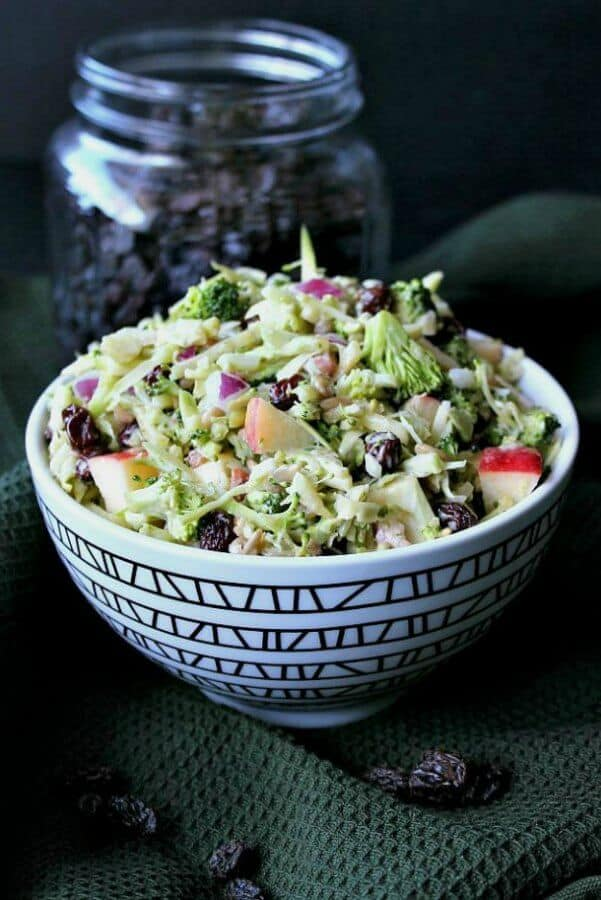 Front view of black & white bowl filled with apple broccoli salad.