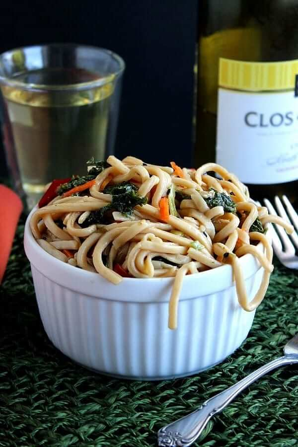 Noodle Pasta Salad is overflowing a white bowl with a bottle of white wine in the back.
