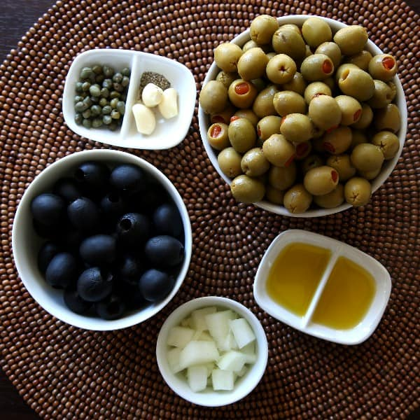 Tapenade ingredients in different shaped small white bowls.