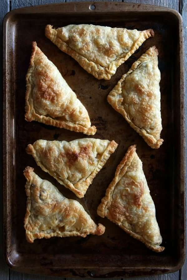 Fresh out of the oven baking sheet that's filled with vegan apple turnovers.
