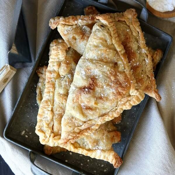 A square tin pan is filled with golden brown vegan apple turnovers.