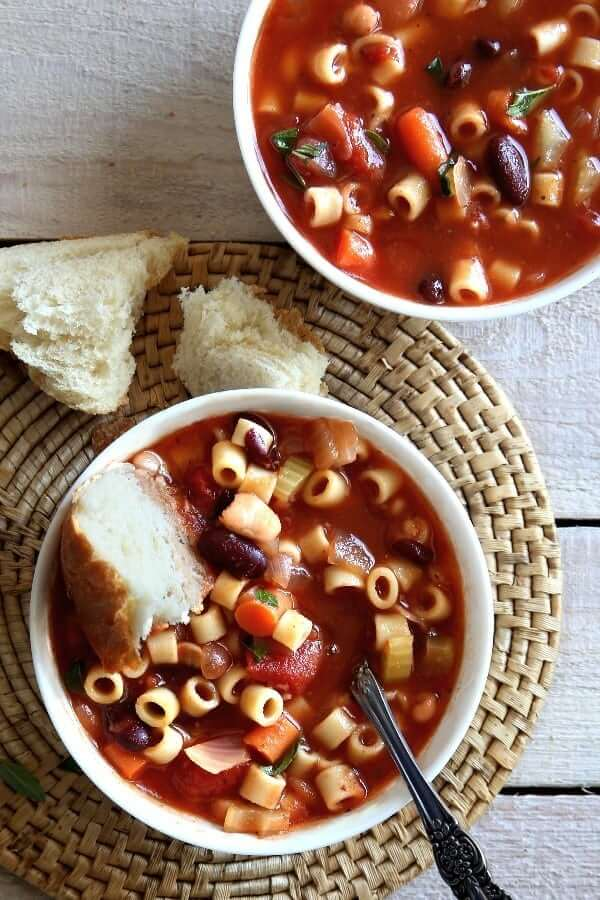 Two white bowls in an overhead photo filled with pasta and beans soup with bread dunked in one.
