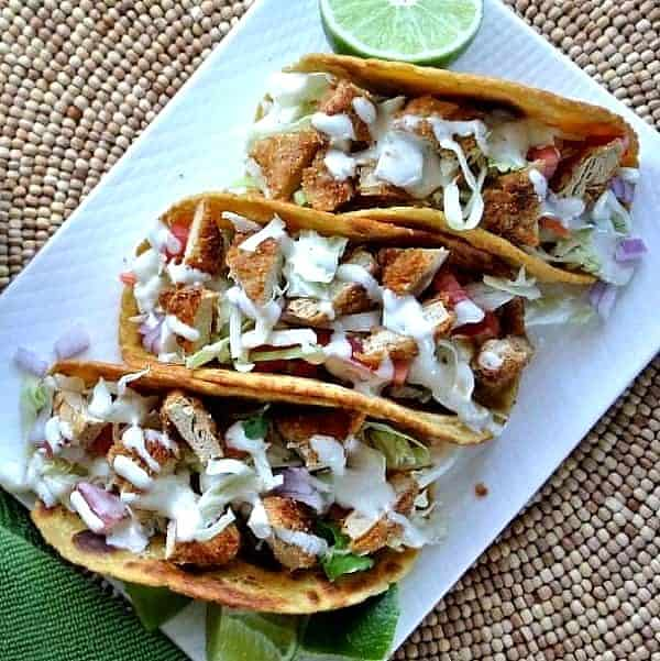 Overhead view of three meatless chicken filled tacos on a white rectangular dish.