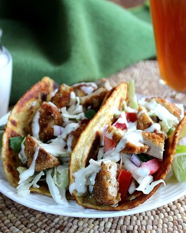 Close front view of two big fat vegetarian tacos filled with veggies and more.