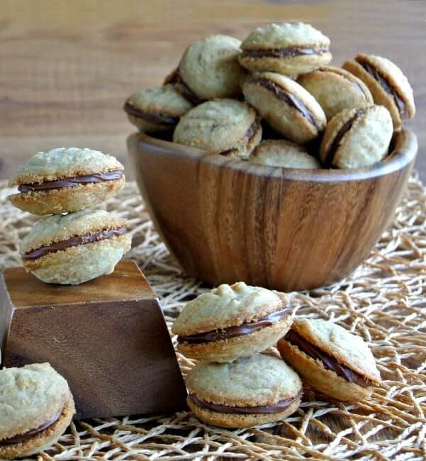 Sandwich Cookies are shaped oval on the top and the bottom and are filling a wooden bowl.