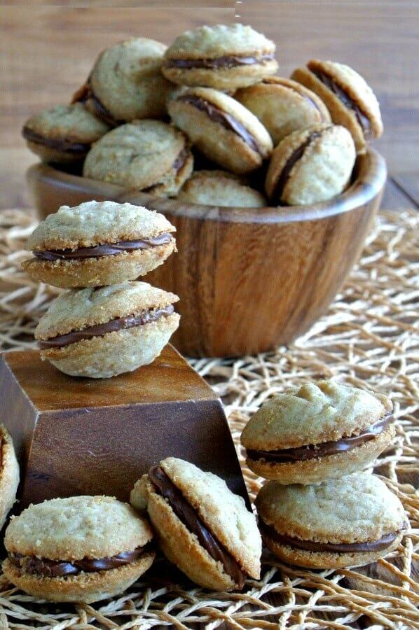 Chocolate filled shortbread sandwich cookies angles in all directions on a woven mat.