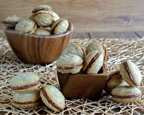 Shortbread cookies filled with chocolate frosting are piled into wooden bowls.