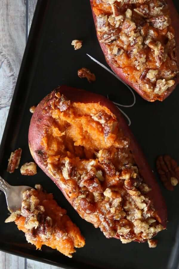 Overhead photo of two dressed and baked sweet potatoes with a forkful sitting next to them.