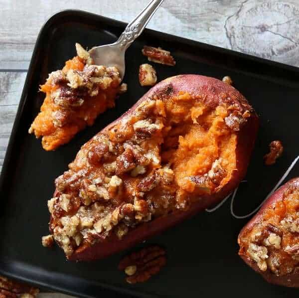Overhead view of two stuffed sweet potatoes with pecans topping on a black tray.