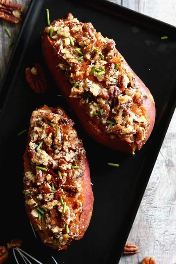Two baked potatoes fresh out of the over with a crunchy sweet pecan topping.
