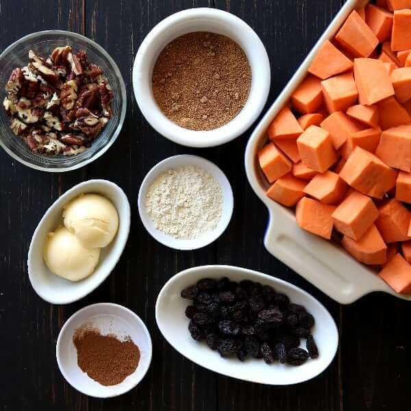 Seven ingredients displayed in separate dishes for the recipe Sweet Potato Casserole with pecans.