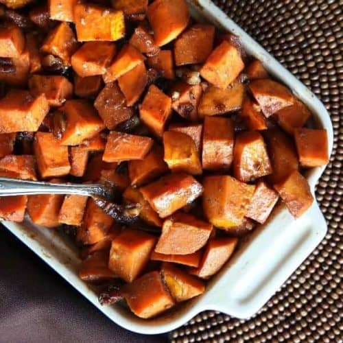 Close up square photo of baked sweet potato casserole with pecans.