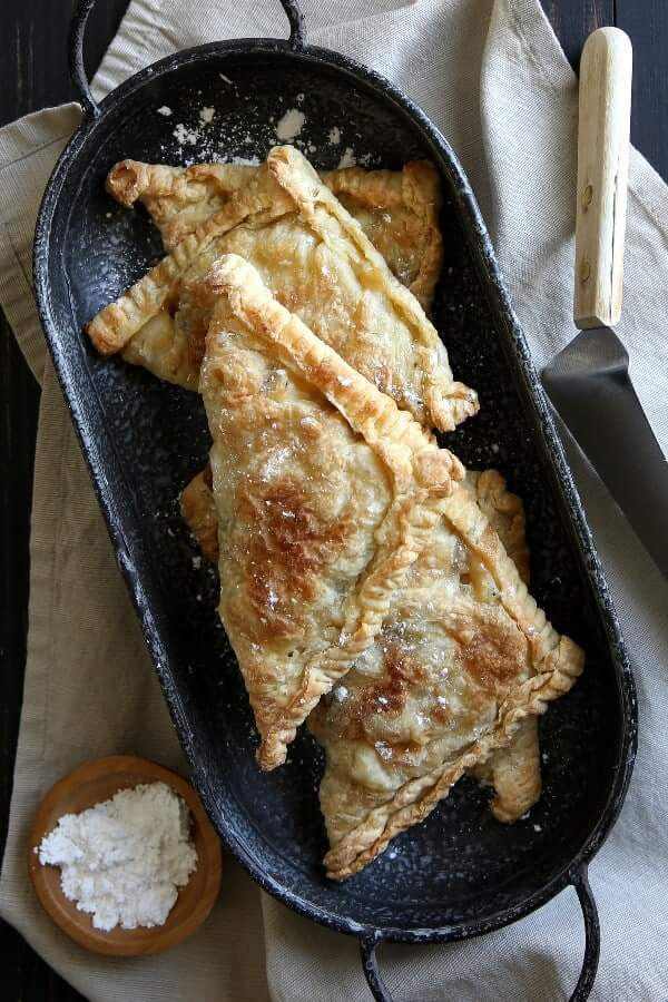 Overhead view of six Apple Turnovers with puff pastry tunovers in an oblong enamaleware pan.