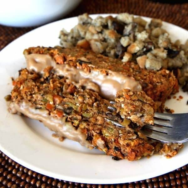 Two slices of Vegan Meatloaf with gravy and mushroom stuffing with a fork picking up a bite.