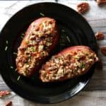 Two stuffed sweet potatoes vegan style dressed and on a black plate.