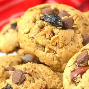 Close up of chocolate chip pecan cookies stacked in a huge pile.