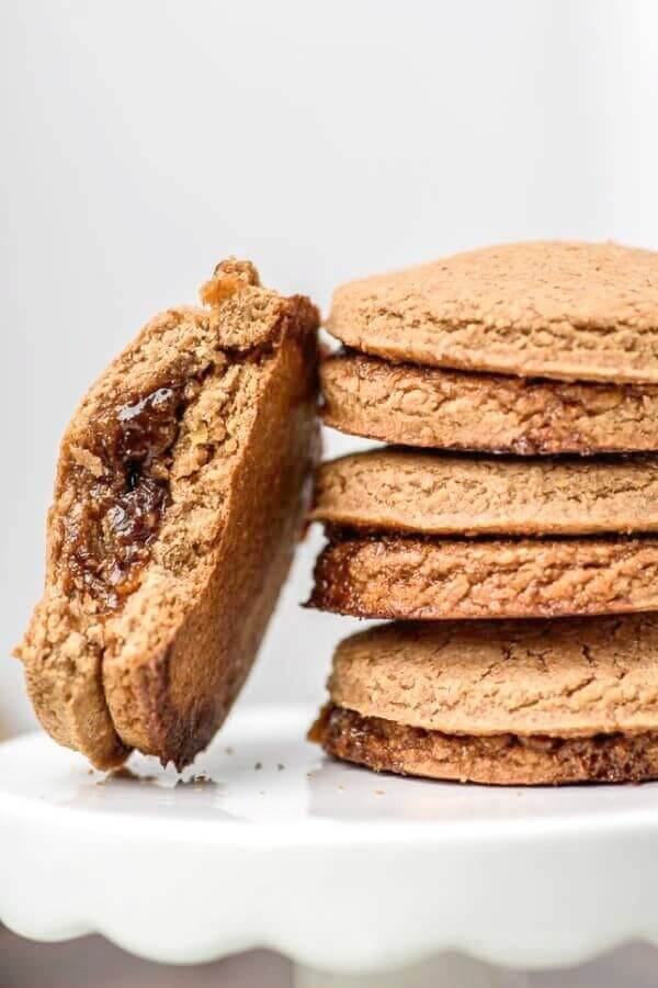 Stack of cookies with one leaning against them with a bite taken out to show the jam filling.