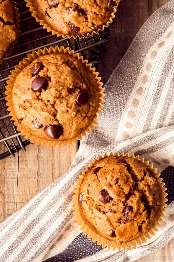 Overhead photo of three baked vegan breakfast muffins on a kitchen striped cloth.