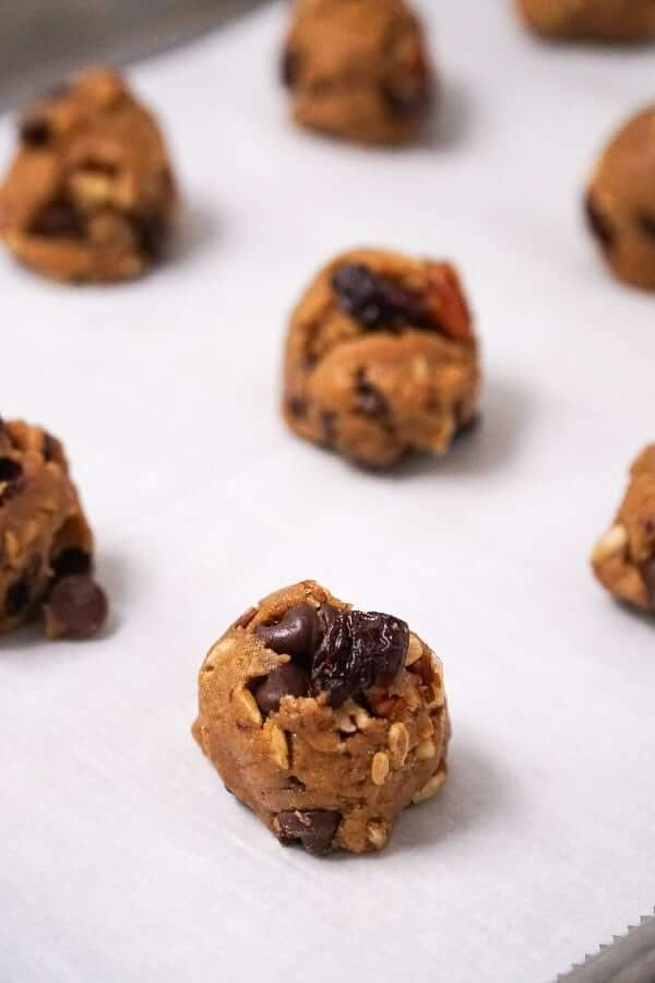 Close up of cookie dough rolled into balls and placed on parchemtn paper in a baking sheet.