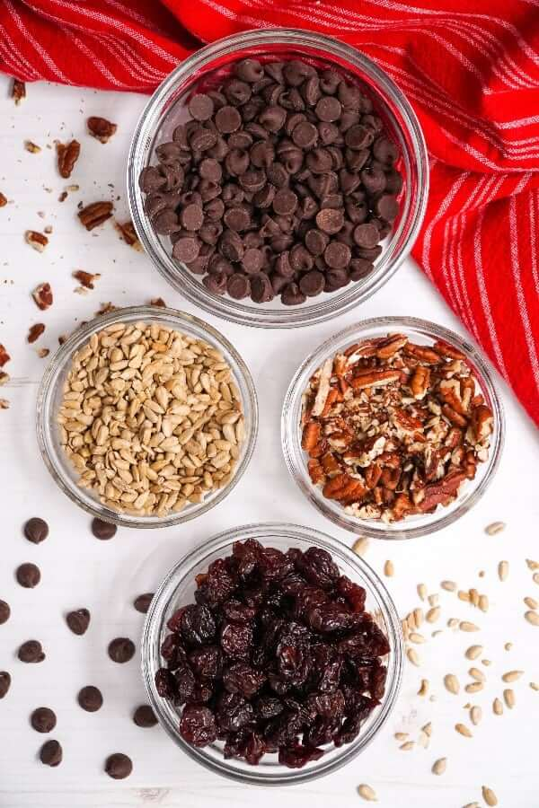 Above head photo of four of the main taste additions, nuts, seeds, fruit, and chocolate.