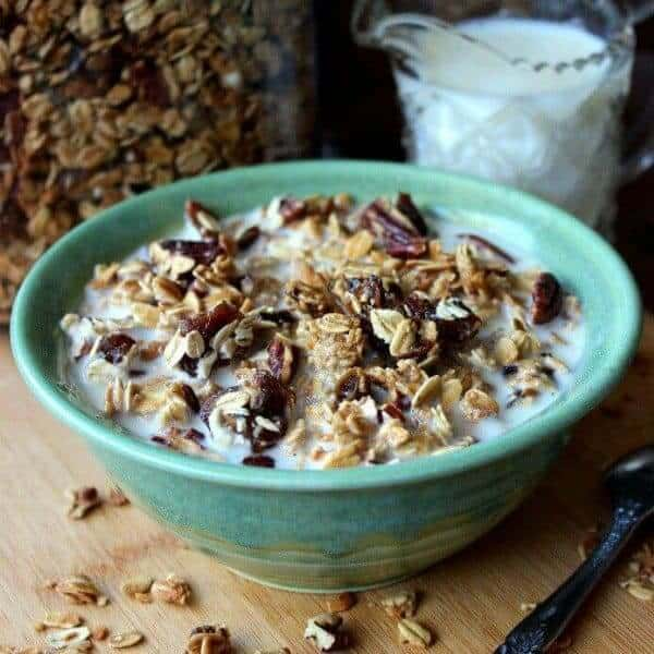 Front view of simple homemade granola cereal in a green pottery bowl.