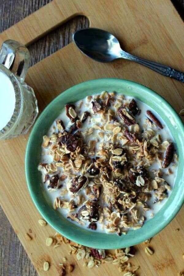 Overhead view of granola and milk in a green bowl sitting on a wooden mat.