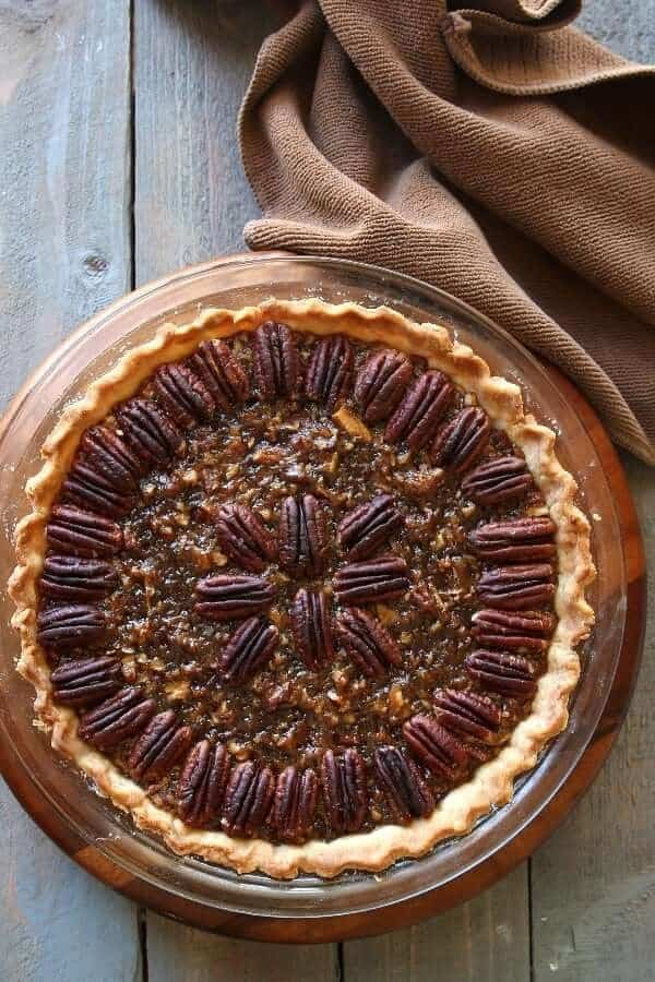 Overhead photo on one complete healthy vegan pecan pie recipe on a wooden trivet