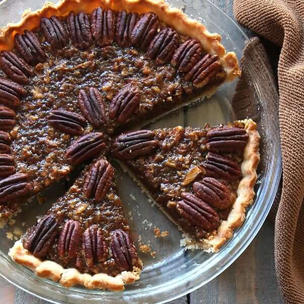 Overhead view of a vegan pecan pie with one slice missing and two slices cut.