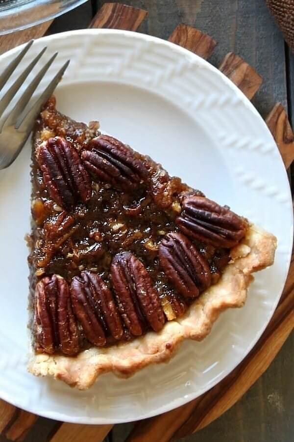 Overhead shot of one slice of pecan pie on a white plate.