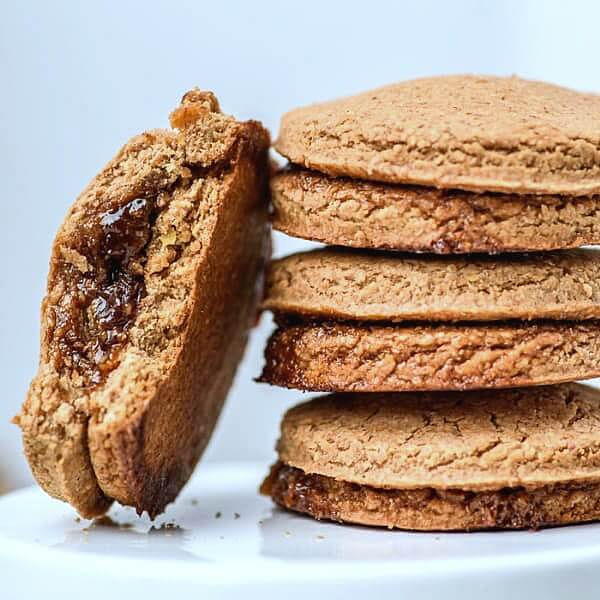 Stack of baked cookies with one leaning on the left with a bite taken out of it to show the jam filling.