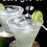Two flared glasses on silver beaded coasters are filled with lime colored margaritas. Lime rings as garnish.