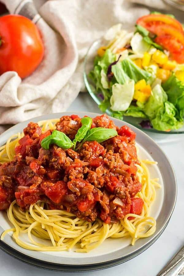 Spaghetti sauce on spaghetti with a salad at the back.