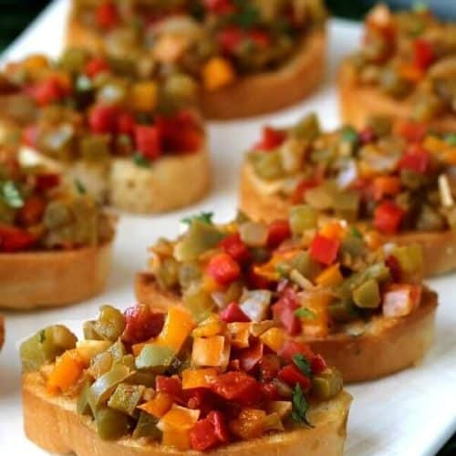 Angled and close-up view of little toasts loaded with colorful diced bell peppers.