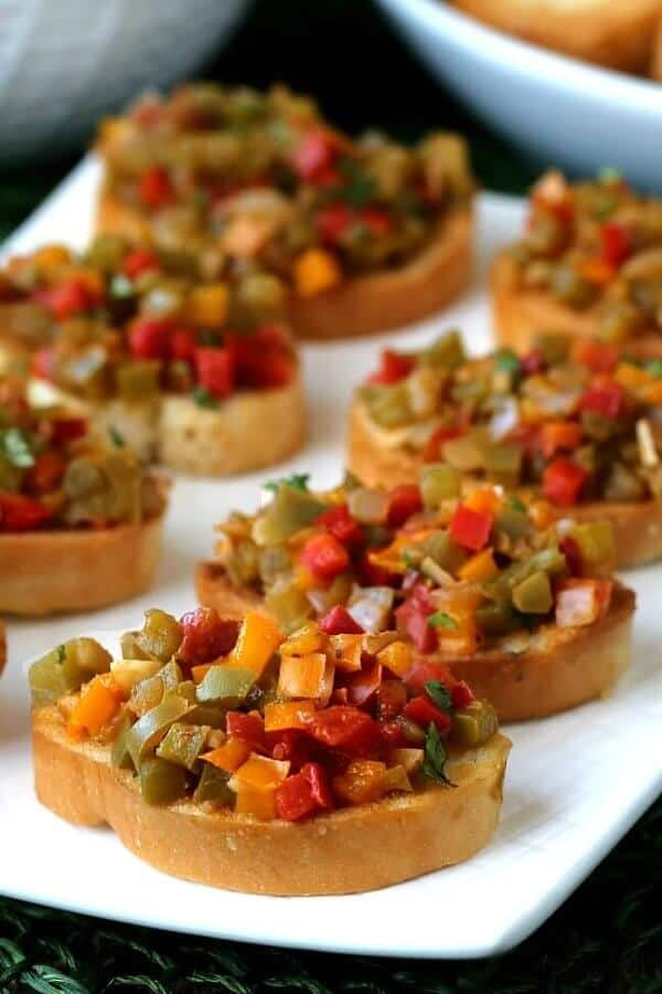 Angled and close-up view of little toasts loaded with colorful easy bruschetta recipe.
