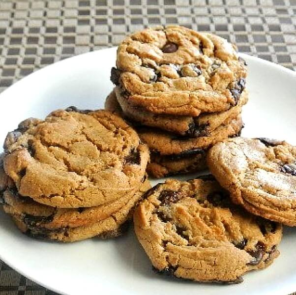 Eight big cookies stacked and spilling all ove a plate.